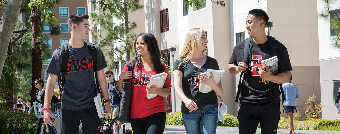 Photo of students walking with their textbooks.